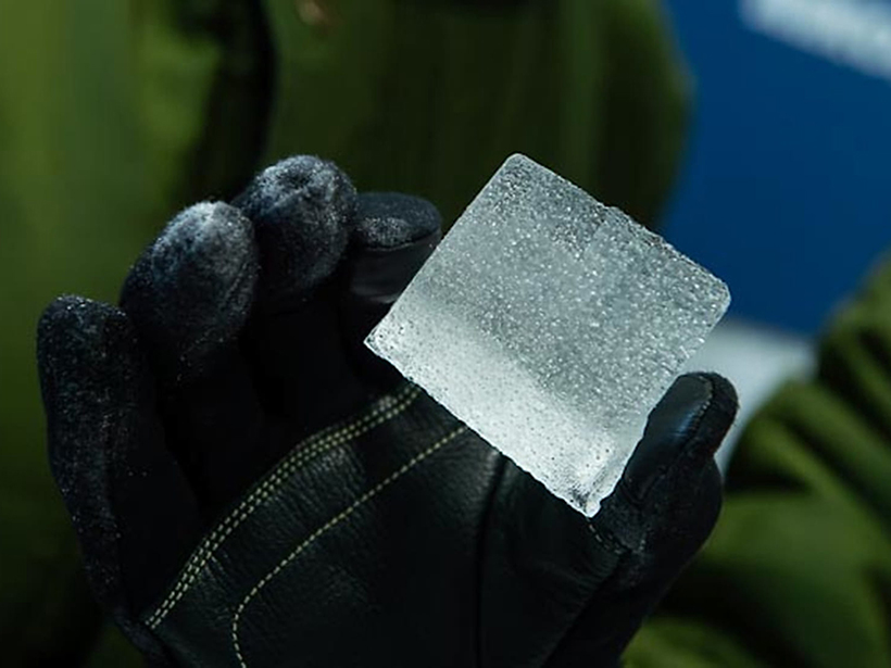 A gloved hand holding an ice core