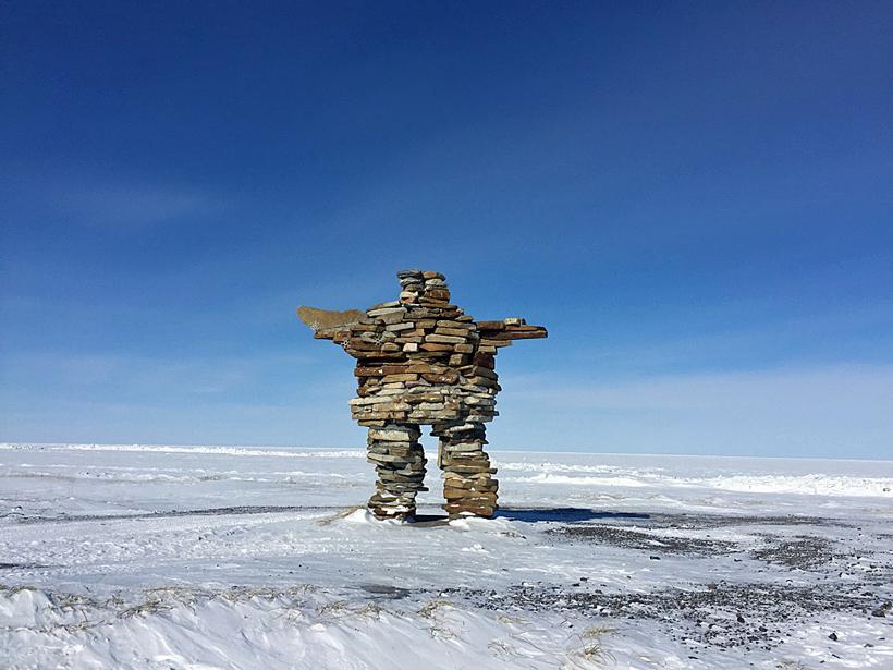 An Inuit stone landmark called an inukshuk overlooks the sea ice at Kuujjuarapik, Nunavik, Canada.