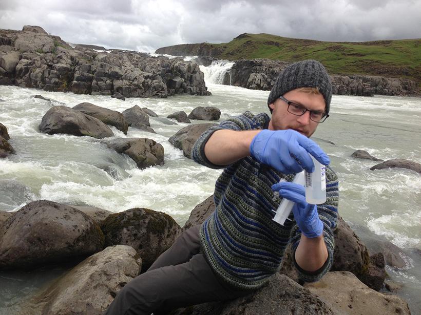 Photograph of biogeochemist Jordon Hemingway collecting a sediment sample from the Thjórsá River in southern Iceland
