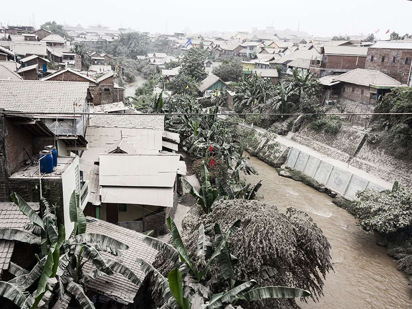 Photo of an ash-covered, densely populated tropical neighborhood and canal