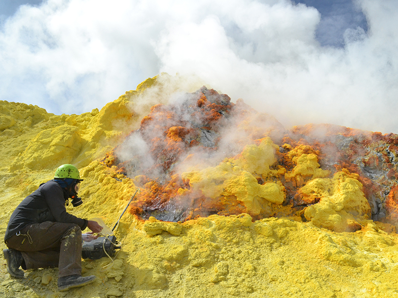 A person collects a sample near yellow rocks and steam.