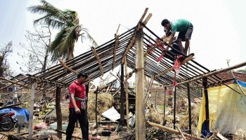 Residents in Odisha, India, rebuild houses destroyed by a cyclone in May 2019