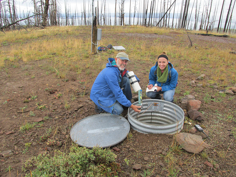 Two smiling scientists kneel to check equipment in an underground seismometer.