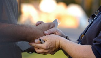A Federal Emergency Management Agency worker holds a disaster victim's hand.