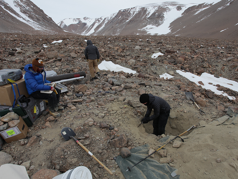 Three scientists, one digging a hole, sample soil from a dry valley in Antarctica.
