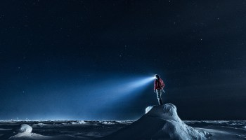 A scientist with a headlamp stands on an ice outcrop in the Arctic night
