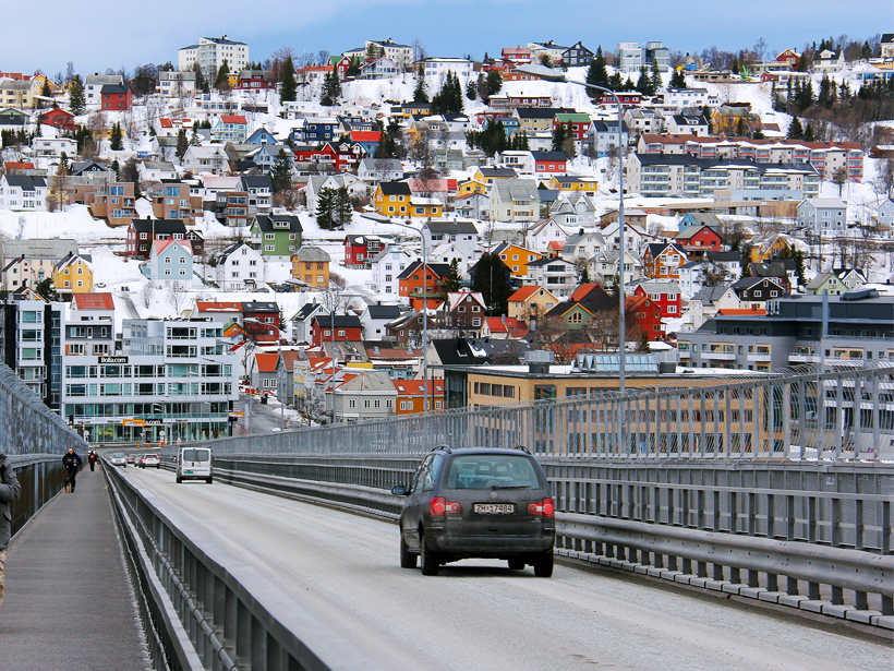 A clean two-lane road leads into a sunny winter day in Tromsø, Norway.