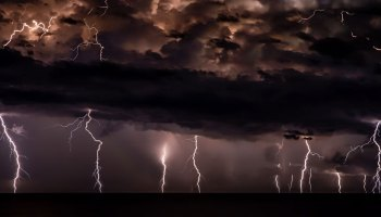Multiple lightning strikes descend from clouds at night
