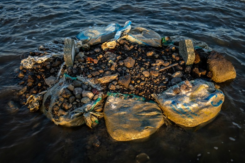 Frayed plastic bags of rubble anchor a drowned gravesite.