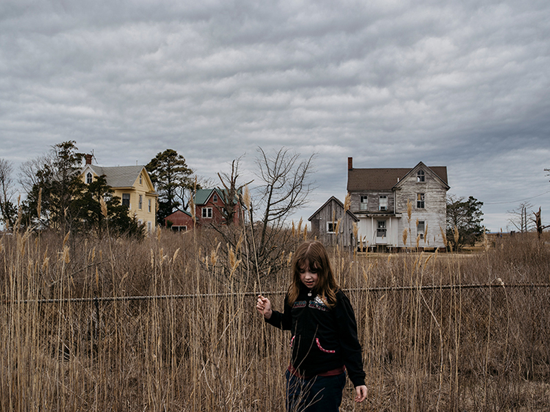A second-grade girl beside a chain-link fence and tall grass.