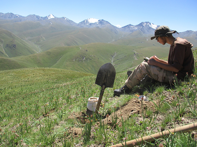 Geologist, with a shovel planted in the foreground, takes notes while overlooking green hills and snowcapped peaks.