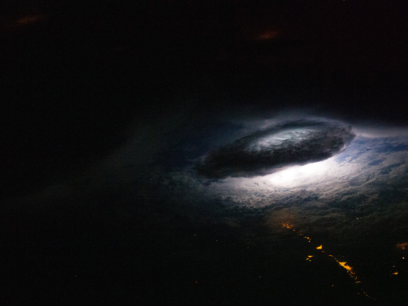 Satellite image of lightning flashing inside a giant thunderstorm over the bright terrestrial lights of Bolivia