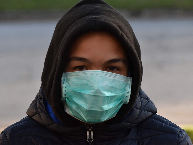 Person wearing a hooded jacket and surgical mask
