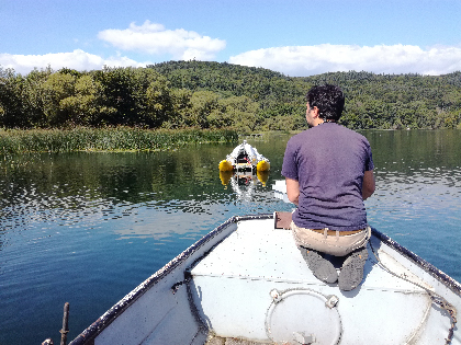 A scientist crouching in a boat checks a hydrophone unit suspended beneath a raft in Laacher See.