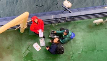 Overhead view of three students aboard a ship deck collecting water samples