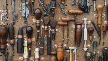 A lot of woodworking tools hang from pegboard