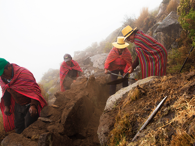 An image of villagers from Huamantanga constructing a shallow stone canal to divert water down a hillside