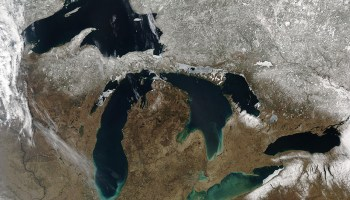 A springtime satellite view of the five Great Lakes shows the snowline roughly following the U.S.–Canadian border.