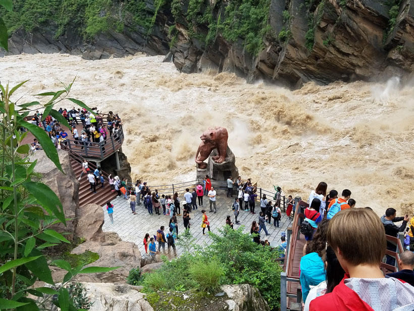 Tourists stand on a platform to view the rapids at Tiger Leaping Gorge along the Jinsha River in China