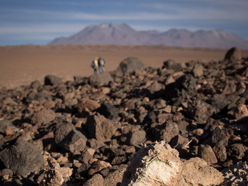 A rock pile in the Atacama Desert, Chile, with one rock in focus and two people standing in the background