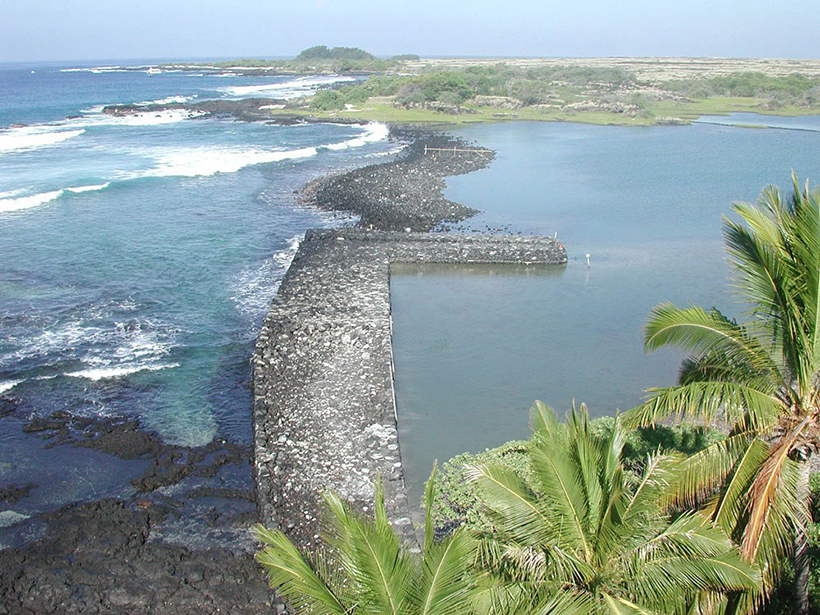 Photo of a low rock jetty separating the ocean from a fish pond