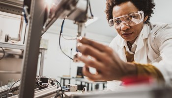 African American woman adjusts a tool in a science lab.
