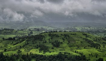 A dark, cloudy sky above rolling green hills near Jawhar in western India