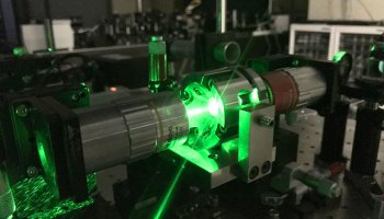 A green laser beam streams between two parts of a cylindrical instrument.