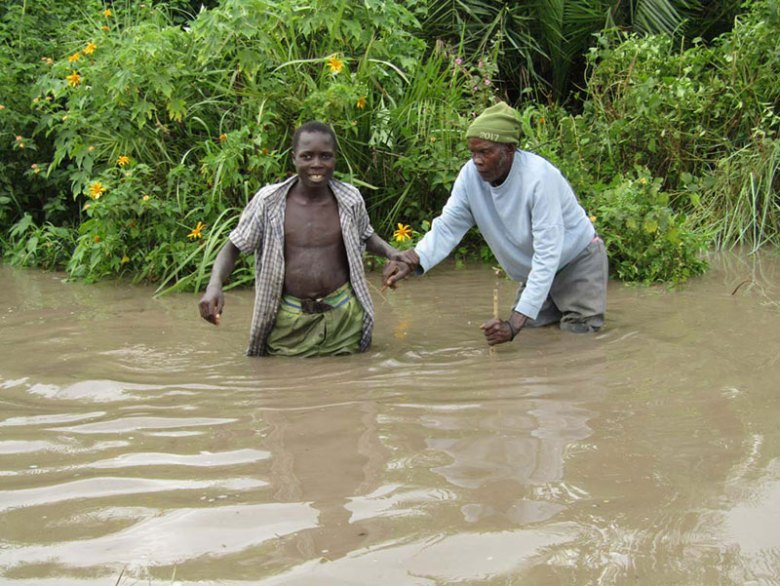 Two men stand in floodwaters above their knees, the younger man holding the arm of the older man, who is leaning on a cane in the water.