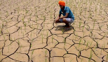 A farmer crouches on dried, cracked soil on his farm in Punjab