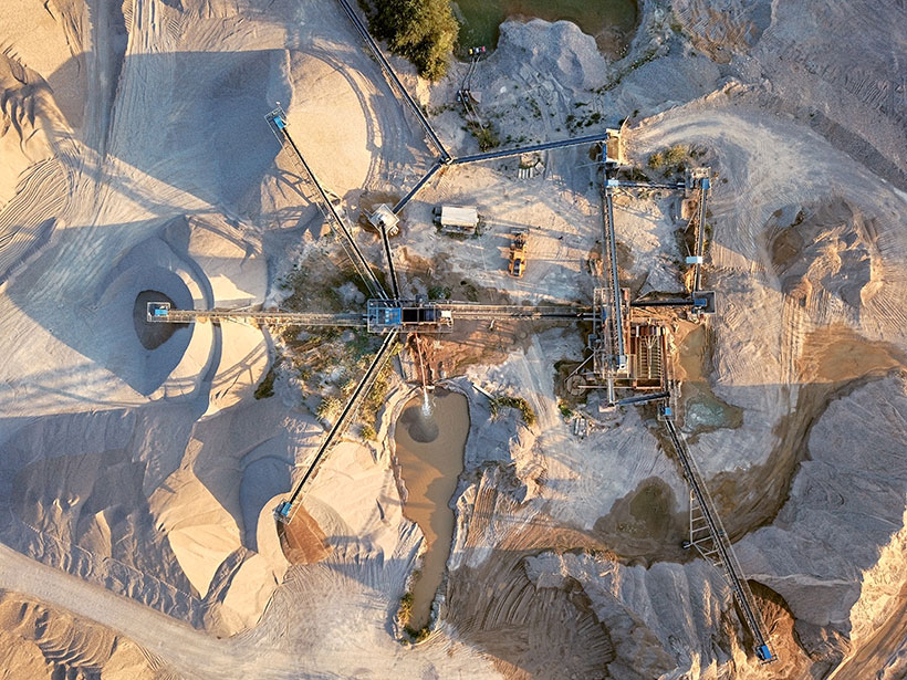 Aerial view of a massive sand-mining machine in the desert