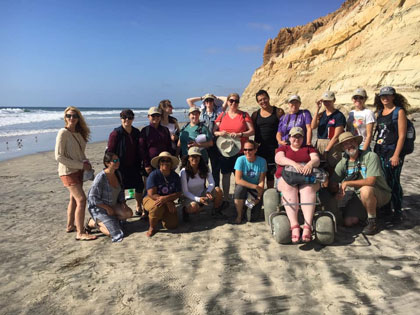 Group of people gathered on a beach with a rock formation in the background