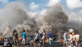 People stand in a scrapyard as dark smokes billows from several small fires.