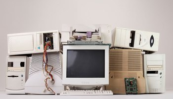 Artfully arranged pile of obsolete computer hardware, including monitor and towers
