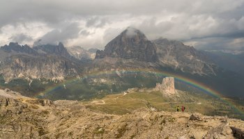 A rainbow arcs over two unrecognizable persons in the cloudy Cinque Torri region of the Dolomites, Italy.