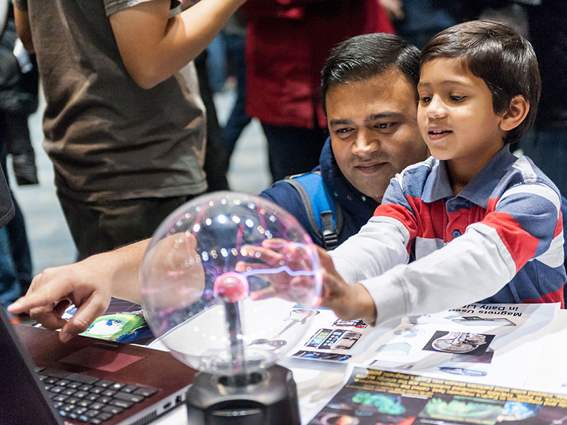 A father and son crouch in front of an interactive science exhibit that includes a plasma globe