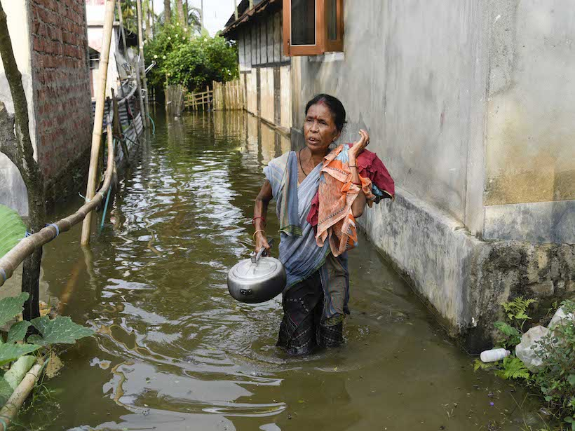 A woman walks through knee-high floodwaters in a narrow street in Assam, India.
