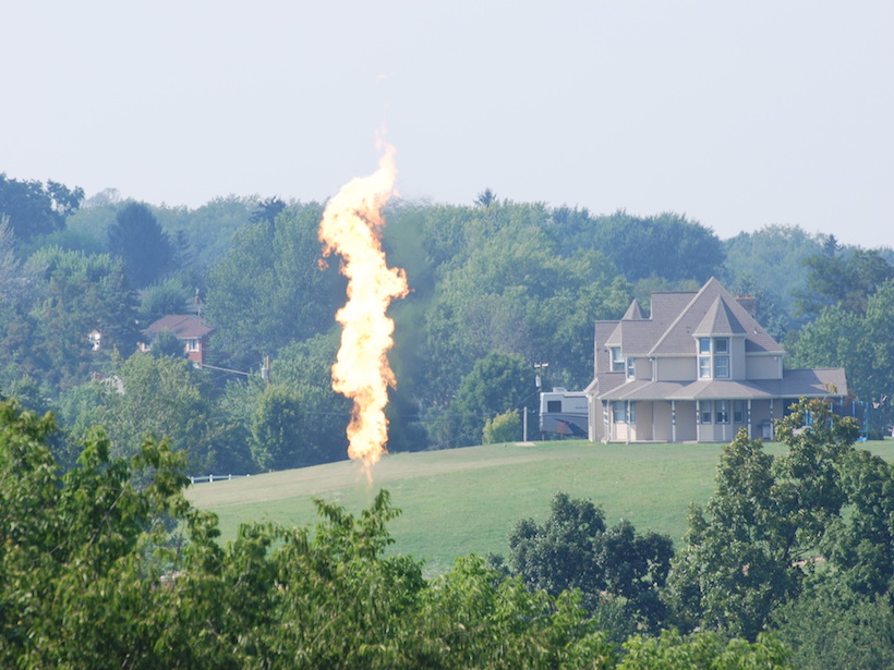 Smoke and flames rise up from a well pad in proximity to houses