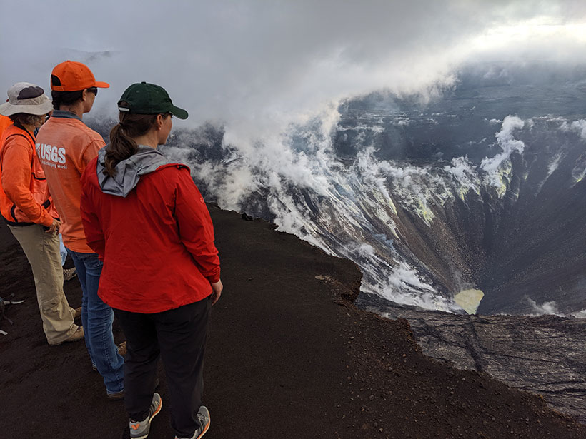 Scientists stand at the crater rim at Kīlauea Volcano on 26 October 2019