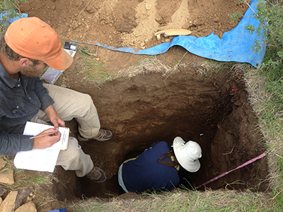 A researcher crouches in a deep pit collecting soil samples while another takes notes.