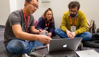 Three scientists sitting on the floor around a laptop