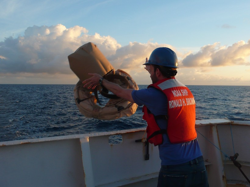 Shane Elipot deploys an instrumented surface drifter from a research ship in 2012 in the North Atlantic Ocean