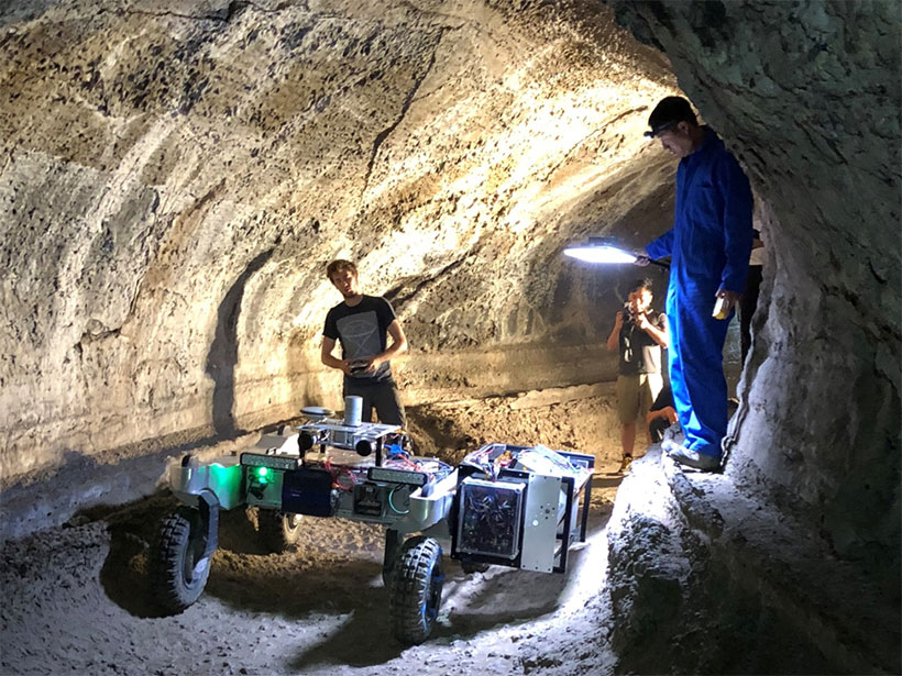 Researchers stand with a rover robot inside a lava tube cave at Lava Beds National Monument in California