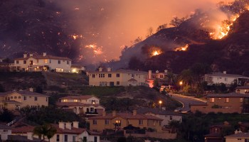 Homes on a hillside with fires in the background