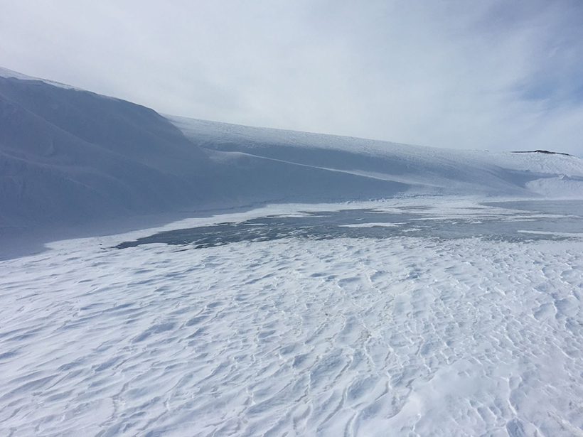 Aerial view of snowdrifts at a lake in the northern foothills of the Brooks Range in Alaska