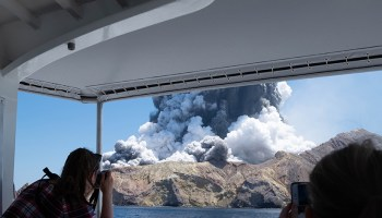 Tourists take photos of black clouds during the eruption at Whakaari/White Island in 2019.
