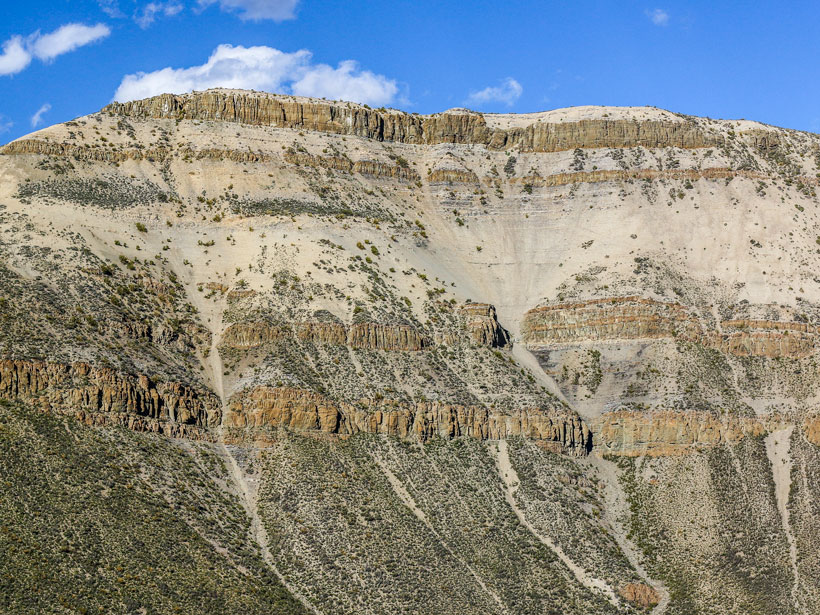 On a mountainside in El Manzano, Mendoza Province, Argentina, volcanic rock intrusions contrast with surrounding organic-rich shale