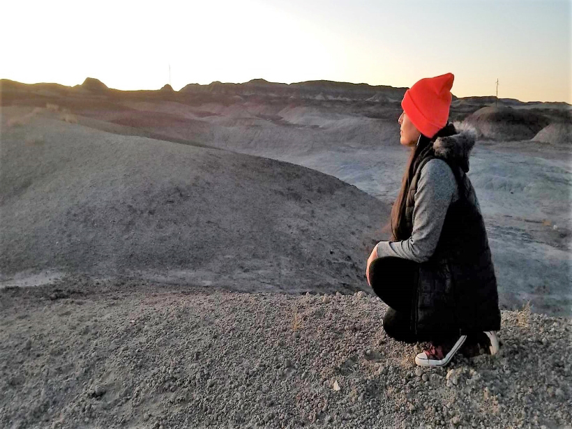 A woman in profile kneels, looking out over Indigenous land in Arizona.