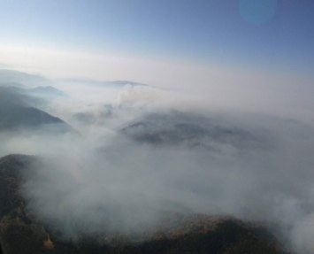 Areal view from a helicopter of smoke from the Camp Fire hovering over the landscape