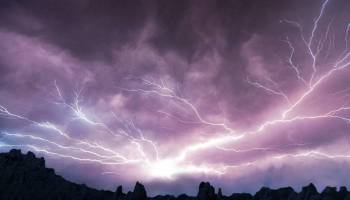 Lightning flashes over jagged cliffs
